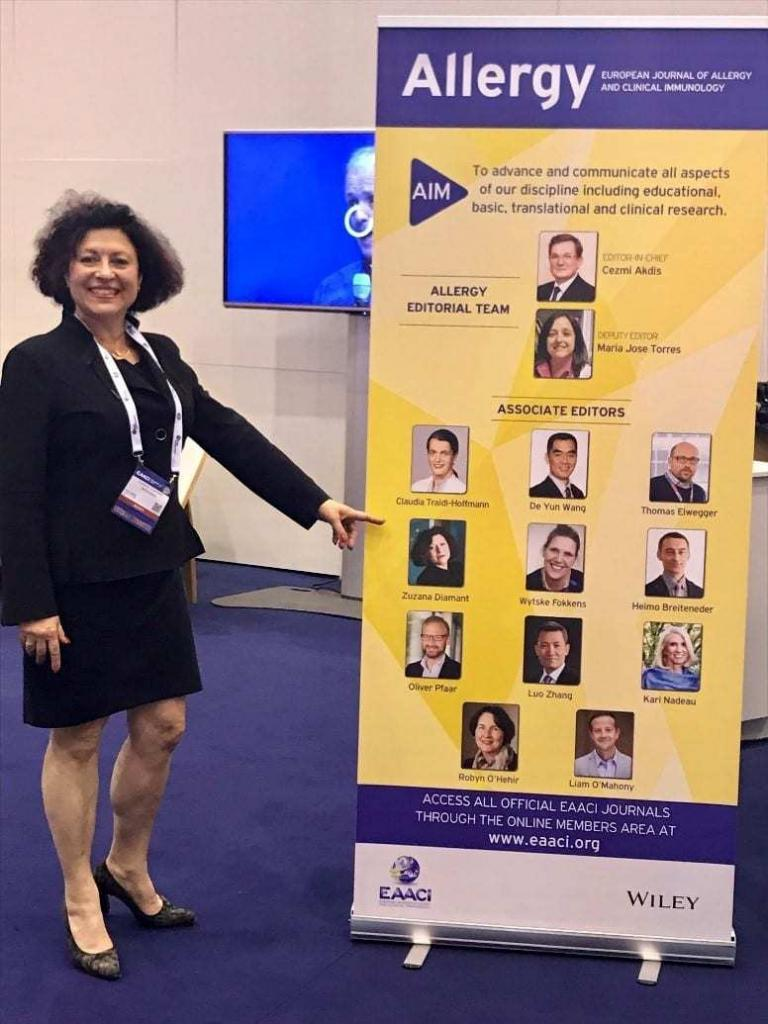 Zuzana Diamant shows the team the poster that lists her as an Associate Editor for the European Journal of Allergy and Clinical Immunology.