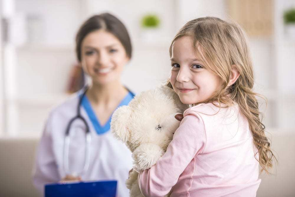 Little girl with teddy bear smiling at camera, doctor in background