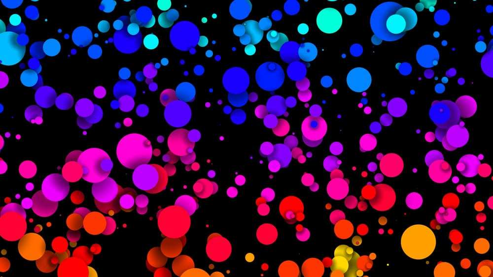 Graphic depicting multi-colored circles of various sizes on black background