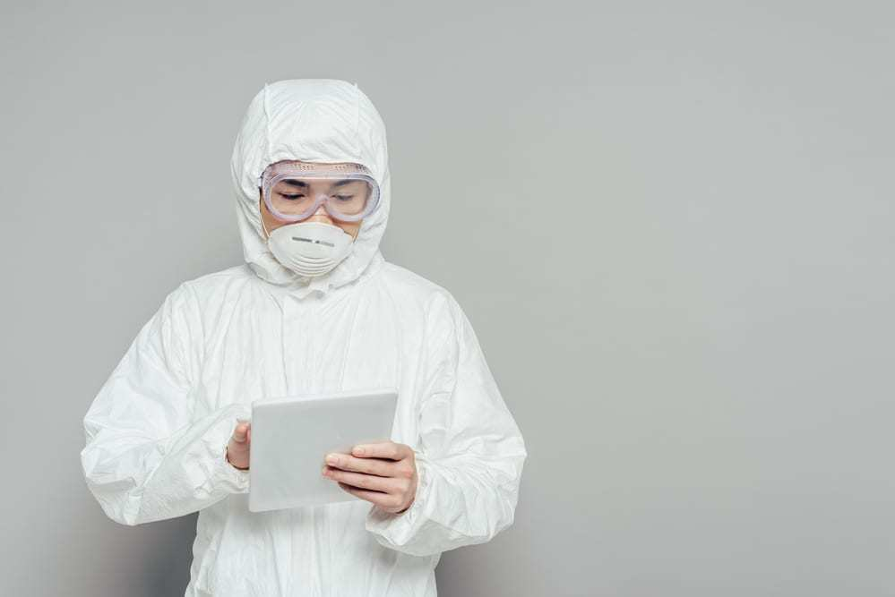 Healthcare worker in PPE using tablet in front of gray background