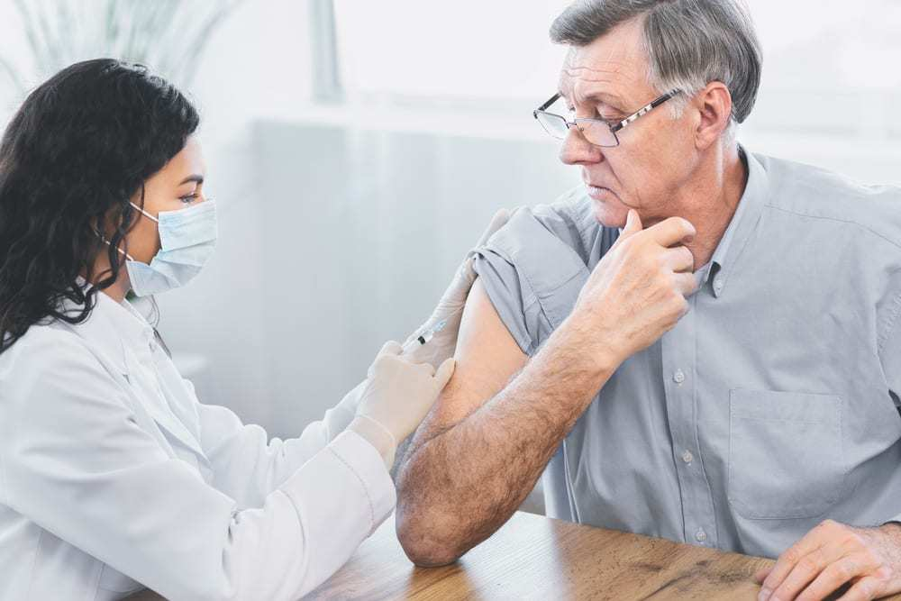 Older Man Receiving Vaccine Injection from Young Healthcare Worker Wearing Face Mask