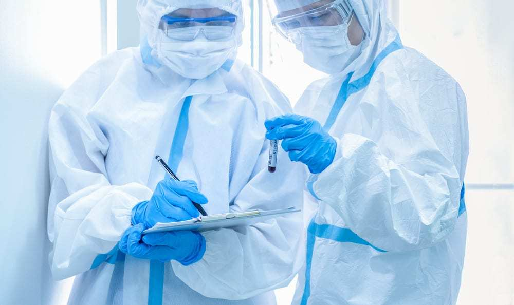 Two healthcare workers in personal protective suits, one holding blood sample, the other writing on chart