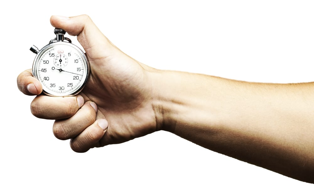 Hand holding stopwatch, white background