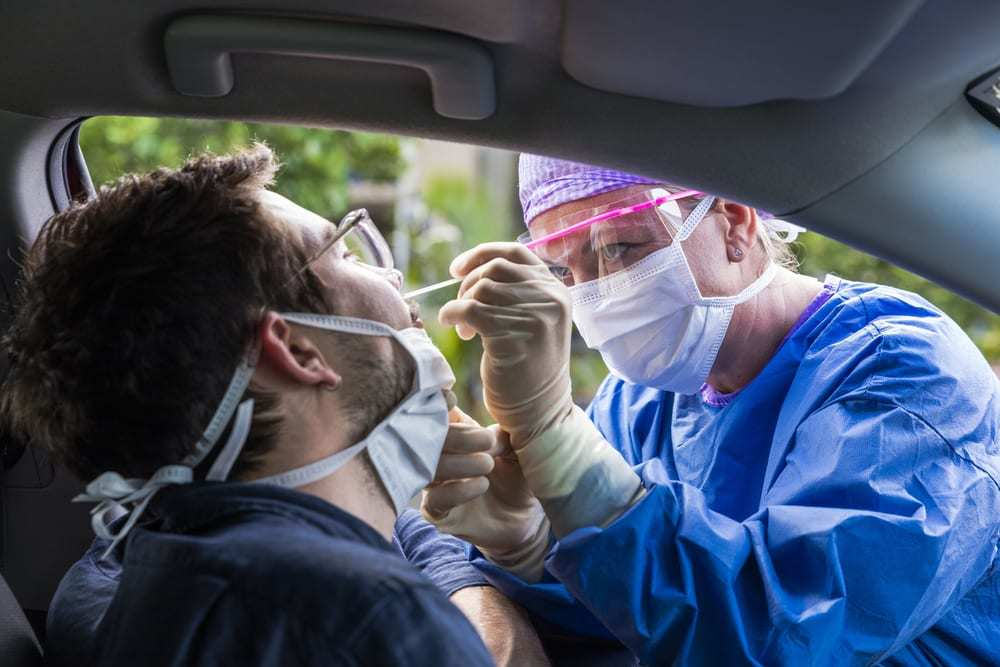 Health care worker in protective gear taking a nasal swab of a man in a car