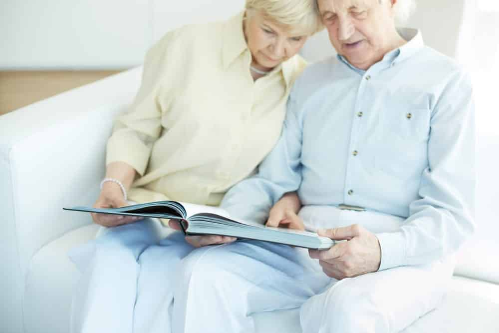 Senior couple on couch looking at book