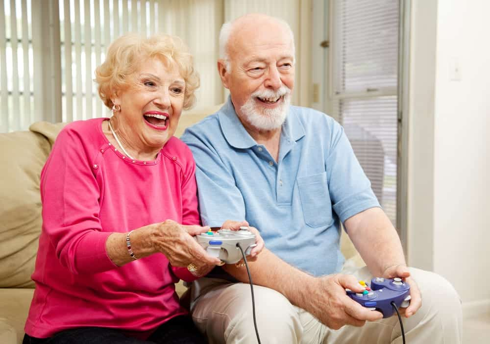 Smiling senior couple playing video game
