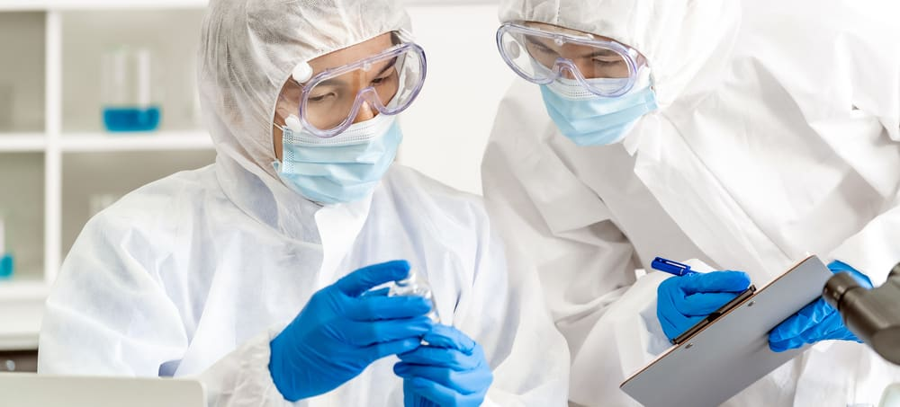 Two scientists in PPE examine vaccine, write on clipboard