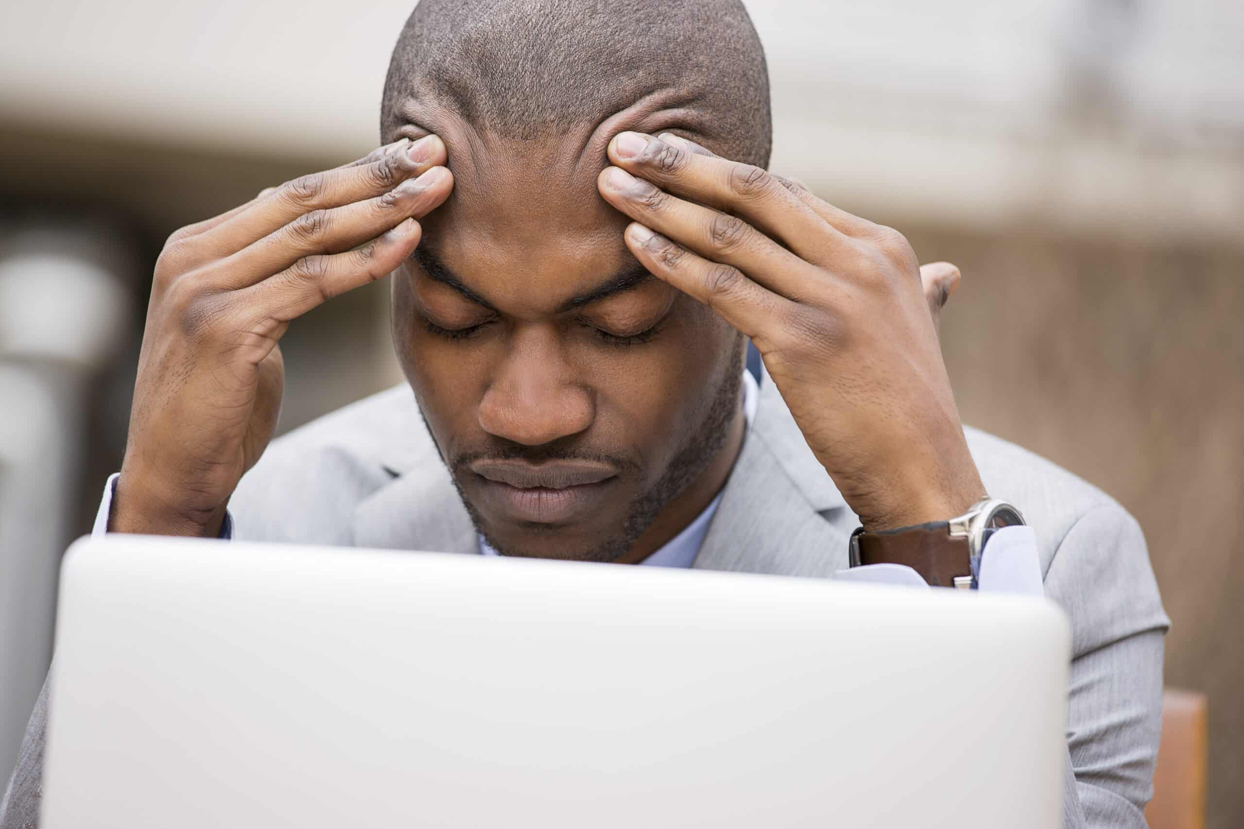 Stressed young man rubbing forehead in front of laptop