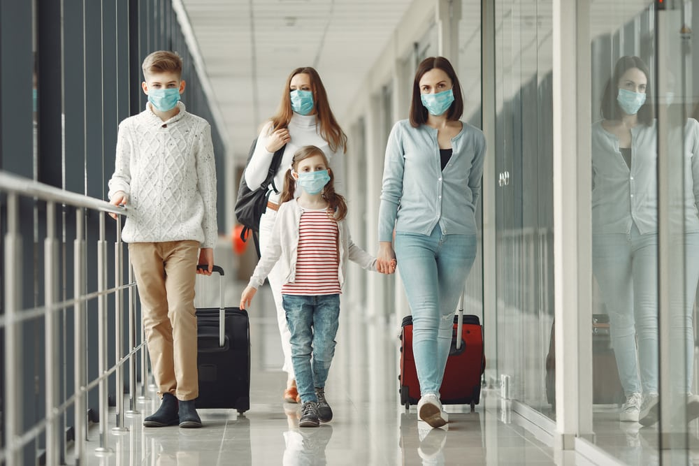 Family wearing face masks at the airport, rolling luggage