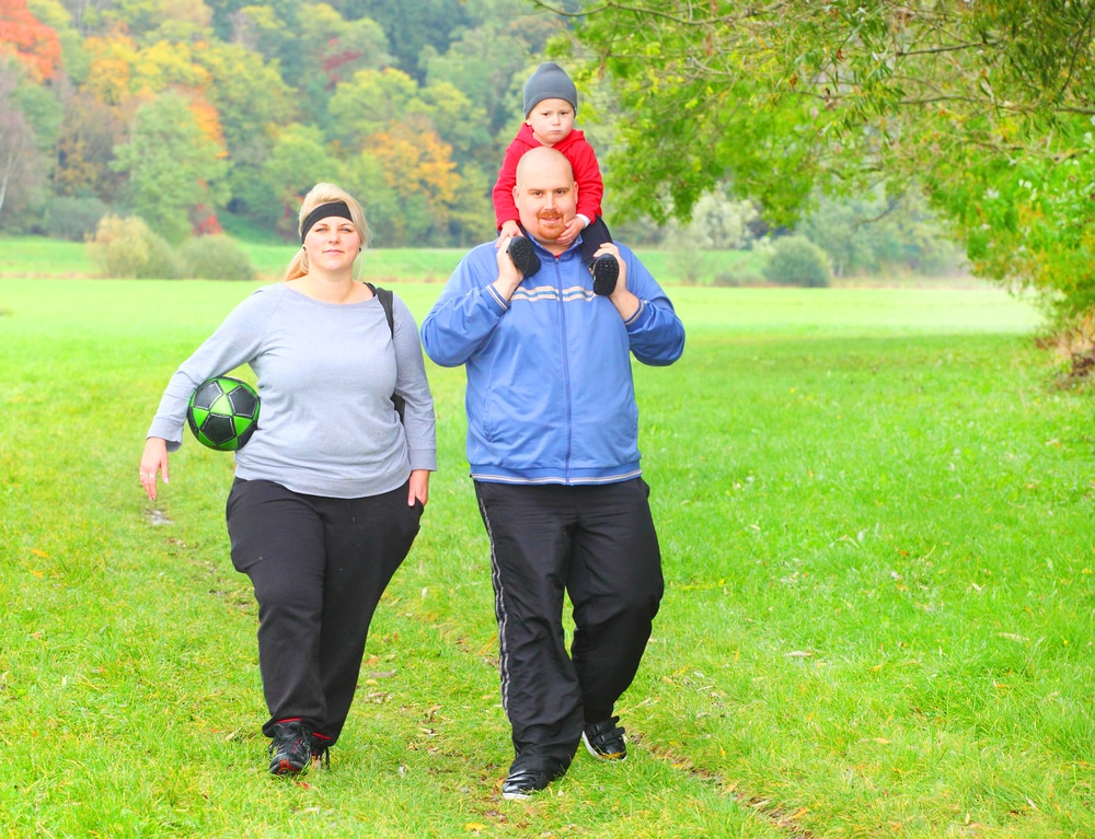 Overweight couple in athletic gear walking outside, toddler son on dad's shoulders